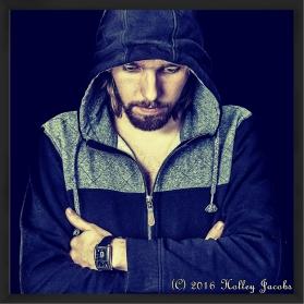 A guy in a black hoodies looking down.