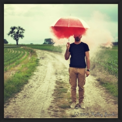 Guy holding an umbrella in the middle of a field